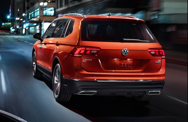 Rear end of a Habanero Orange 2019 Volkswagen Tiguan rolling down a city street at night.