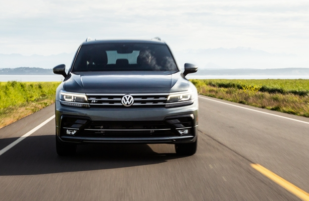 2019 Volkswagen Tiguan drives head-on up a highway out in scenic countryside.