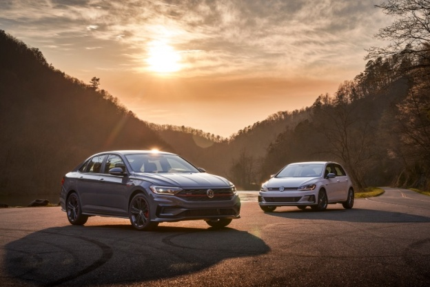 2021 Volkswagen Golf GTI and 2021 Volkswagen Jetta GLI hang out together on a circle of pavement under the setting sun