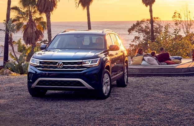 Family relaxes on the coast alongside a 2021 Volkswagen Atlas